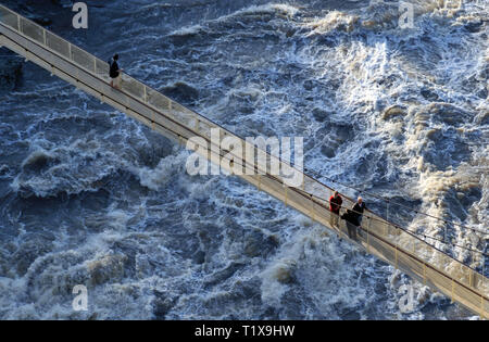 An elevated view of three people on a suspension bridge looking down on the flooded Tamar river in Launceston, Tasmania, Australia. - Stock Photo