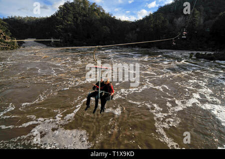 Two people on a chairlift, suspended above the flooded Tamar river in Launceston, Tasmania, Australia. - Stock Photo