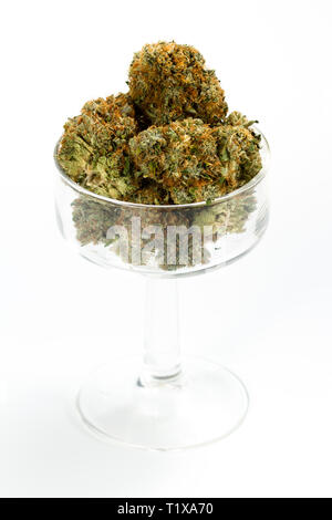 clear glass serving of cannabis buds isolated on a white background - Stock Photo