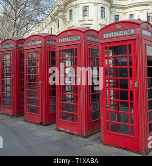 Four red traditional and heritage telephone boxes or kiosks stand in a row on the Strand, London, England, UK opposite Charing Cross Station. - Stock Photo
