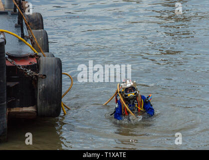 Diver emerges from the river Thames, London, UK, alongside the maintenance boat, after unblocking an underwater drain with a high pressure pipe. - Stock Photo