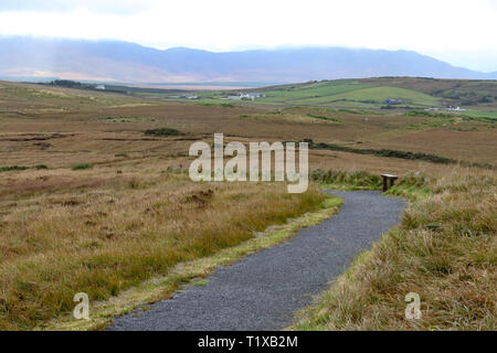 Empty wooden bench on walk at Ballycroy National Park with low cloud over the Nephin Beg Mountains in the distance. - Stock Photo
