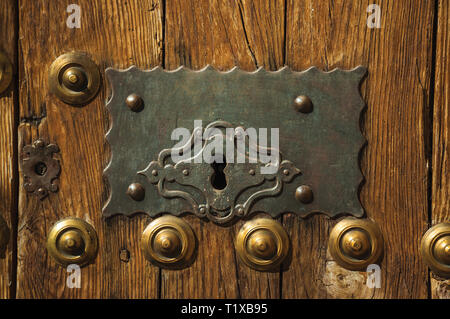 Studs attached to wooden planks and wrought iron keyhole in an old door at Caceres. A charming town with a fully preserved old city center in Spain. - Stock Photo