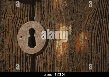 Close-up of wrought iron keyhole in an old wooden door on sundown at Caceres. A charming town with a fully preserved old city center in Spain. - Stock Photo