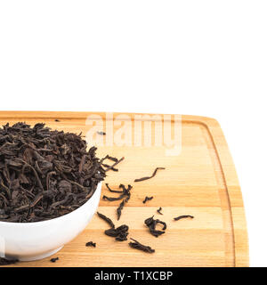 Dried tea is poured into a ceramic cup on a wooden board on a white background - Stock Photo