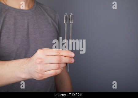 Tuning Fork for hearing tests in hands of young man. Medical equipment of otolaryngologist (ENT). Medical and Healthcare concept. - Stock Photo