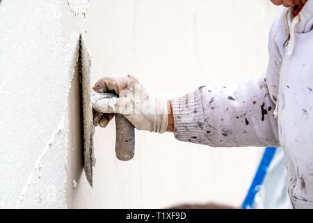 Construction worker plastering and smoothing concrete wall with cement. - Stock Photo