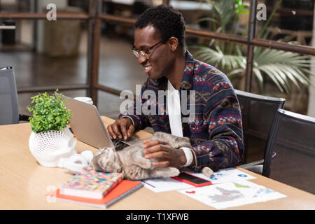 Man being distracted by his cat while working