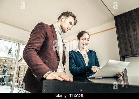 Bearded dark-haired man wearing dark red jacket talking to realtor - Stock Photo