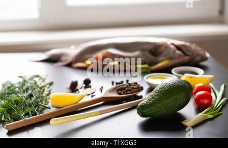 Fresh cooking ingredients on a kitchen table with aromatic potherbs, avocado pear, tomato, spring onion, lemon and spices viewed low angle with a raw  - Stock Photo