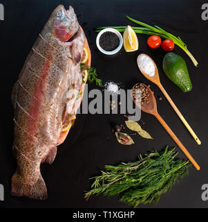 Food flat lay still life of a whole raw fresh trout surrounded by aromatic herbs, spices, lemon, avocado pear, tomato and spring onion to prepare a de - Stock Photo