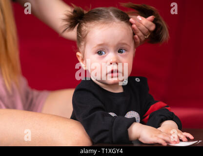 Young mother tying up her little daughters hair into pigtails in a close up view on the kids head and shoulders - Stock Photo
