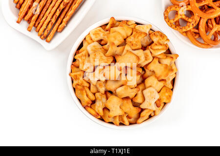 A closeup photo of salty fish crackers, sticks, and pretzels, shot from above on a white background with copy space. Party snacks mix - Stock Photo