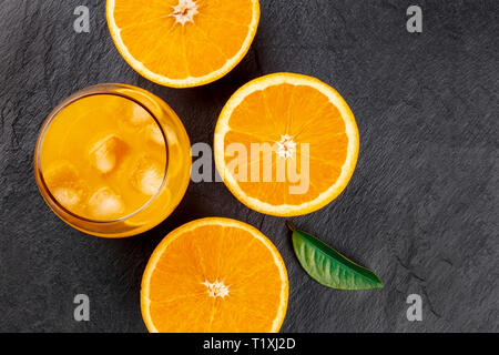 A closeup photo of a glass of fresh orange juice with ice cubes, orange halves and a green leaf, shot from the top on a black background - Stock Photo