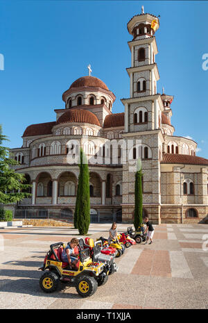Children playing on miniature cars in front of Korca's Orthodox Cathedral, Korca, South eastern Albania. - Stock Photo
