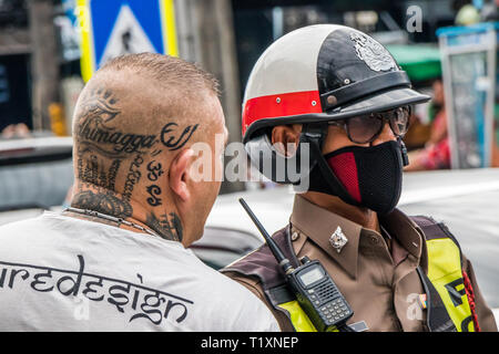 Phuket, Thailand 17th January 2019: Man with tattooed head talking with policeman in Patong Beach. Police often fine tourists for traffic offences. - Stock Photo