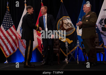 U.S. Acting Secretary of Defense Patrick M. Shanahan shakes hands with the outgoing commander of U.S. Central Command, U.S. Army Gen. Joseph L. Votel, at the Centcom change of command, Tampa, Florida, March 28, 2019. The new commander of U.S. Central Command, U.S. Marine Corps Gen. Kenneth F. McKenzie Jr., is to the right. (DoD photo by Lisa Ferdinando) - Stock Photo