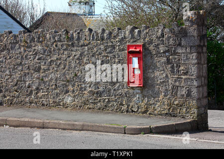 An old King George era letter box embedded in a wall adjacent to the main road through the village, now replaced by a nearby free standing box. - Stock Photo