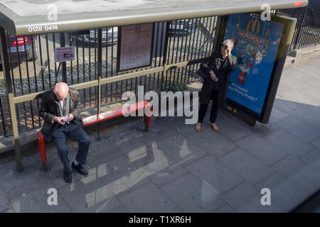 An elderly gentleman wipes his spectacles clean with a cloth, as a lady raises hers to see oncoming buses, on Denmark Hill in Southwark, on 28th March 2019, in London, England - Stock Photo