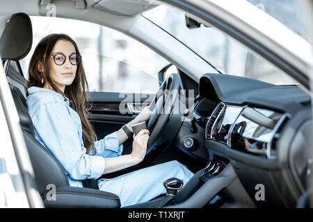 Portrait of a young confident woman sitting on the driver seat of the modern car Stock Photo