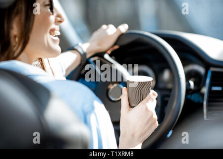 Cheerful woman holding steering wheel and coffe cup while driving a car, close-up view - Stock Photo