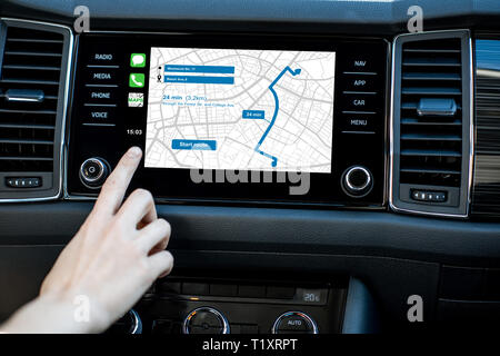 Touching a monitor with navigation map of the modern car, close-up view - Stock Photo
