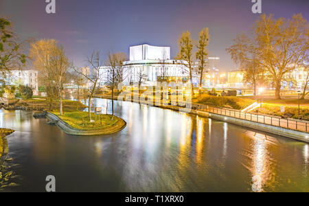 Bydgoszcz / Poland -  Concert hall by nigh - illuminated building reflected in the river. City lights. - Stock Photo