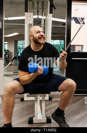 young athlete takes a selfie while doing exercises with the dumbbells in the gym - Stock Photo