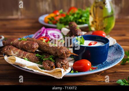 Turkish and Arabic Traditional Ramadan mix kebab plate. Kebab adana, chicken, lamb and beef on lavash bread with sauce. Top view - Stock Photo