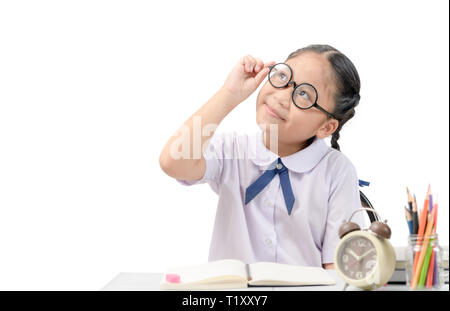 Cute student thinking while doing her homework on table isolated on white background, education concept - Stock Photo