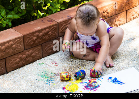 Beautiful little girl draws with finger paints on a white sheet of paper. Creative child development in kindergarten or free time at home. - Stock Photo