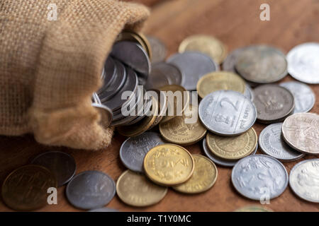 Indian coins spilling out from a burlap sack on a wooden surface. Indian currency background concept. - Stock Photo