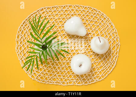 Palm leaves in a vase and white decorative fruits on bright yellow background. Tropical summer theme. - Stock Photo