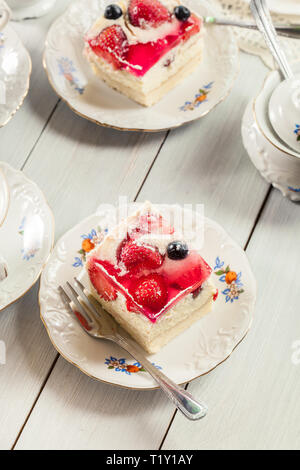 Portions of cheesecake with strawberries, blueberry and jelly served with cup of coffee - Stock Photo