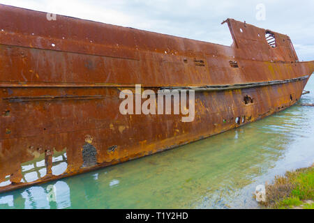 Scuttled rusting hulk of old ship Waverley in shallows of Wairau Lagoons on nature walk. - Stock Photo