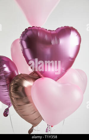 heart-shaped pink and golden air balloons isolated on white - Stock Photo