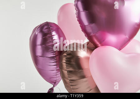 heart-shaped pink and golden festive balloons isolated on white - Stock Photo
