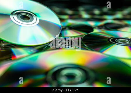 CDs / DVDs lying on a black background with reflections of light. - Stock Photo