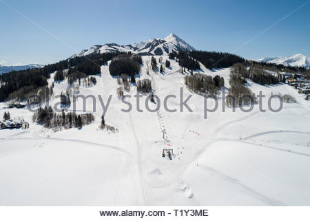 Aerial view of the Gold Link chair lift with the peak of Crested Butte Mountain in the distance. - Stock Photo