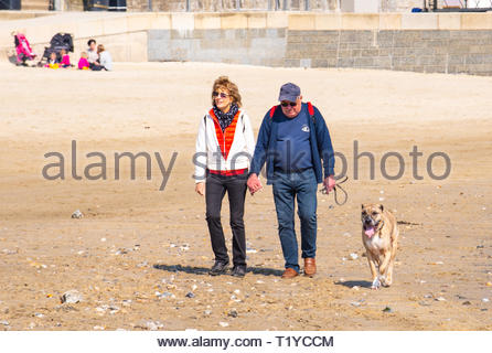 Lyme Regis, Dorset, UK. 29th March 2019. UK Weather: Another day of glorious sunshine and bright blue skies as the seaside resort town of Lyme Regis as the early spring heatwave continues.  Visitors and families enjoy the unseasonably hot weather on the sandy beach. Credit: Celia McMahon/Alamy Live News - Stock Photo
