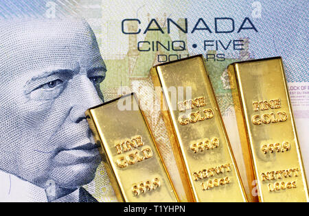 A close up image of a blue Canadian five dollar bill with three small gold ingots - Stock Photo