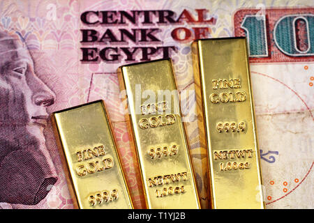 A close up image of three small gold bars on a ten Egyptian pound bank note in macro - Stock Photo