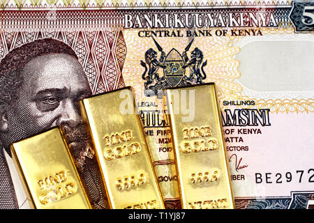 A close up of a Kenyan fifty shilling bank note with three golden ingots in macro - Stock Photo