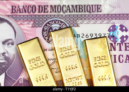 A close up image of a twenty metical bank note from Mozambique with three small golden ingots in macro - Stock Photo