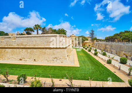 The outer wall of Mdina Fortress is surrounded by scenic ornamental garden, stretching along its bastions and gates, Malta. - Stock Photo