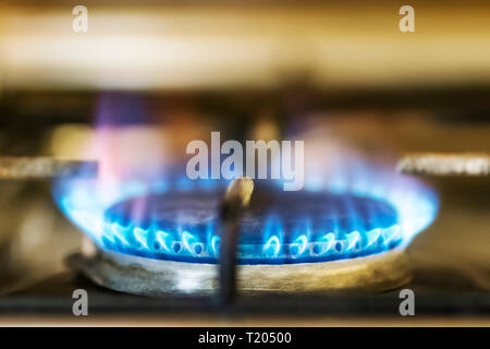 burning blue flame gas on the old stove in the kitchen - Stock Photo