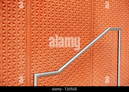 stainless steel handrail or Banister on steps the Cladded wall of terracotta-coloured concrete decorated with Egyptian motifs and 1960s op art pattern - Stock Photo