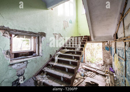 concrete staircase in the old abandoned ruined house indoor on sunny day