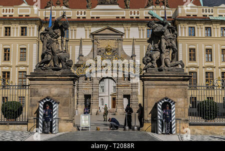 Prague, Czech Republic - September , 18, 2019: Guards at the Battling Titans statues at gate to First Courtyard at Hrad Castle with Archbishops Palace - Stock Photo