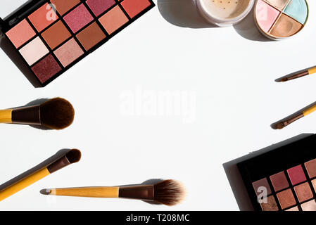 Bright arrangement of make up cosmetics and accessories. Eyeshadow palettes, powder, concealer and natural brushes with bamboo wood handles. Copy spac
